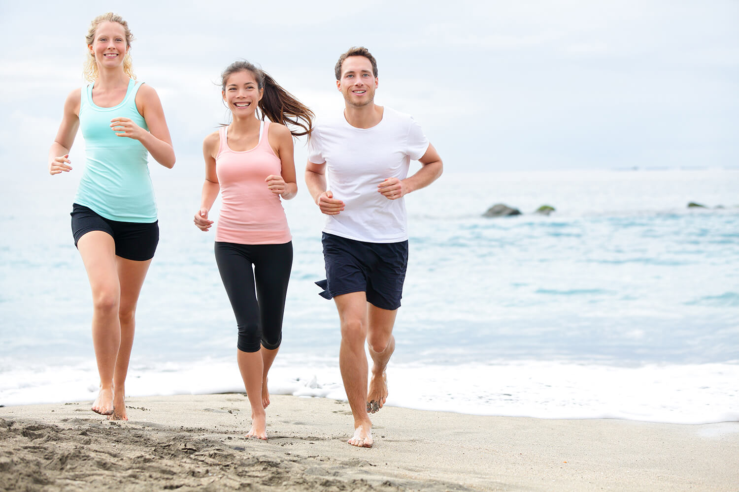 Two women and a man jogging along the seashore