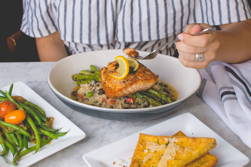a woman holding a fork to eat roasted salmon with asparagus