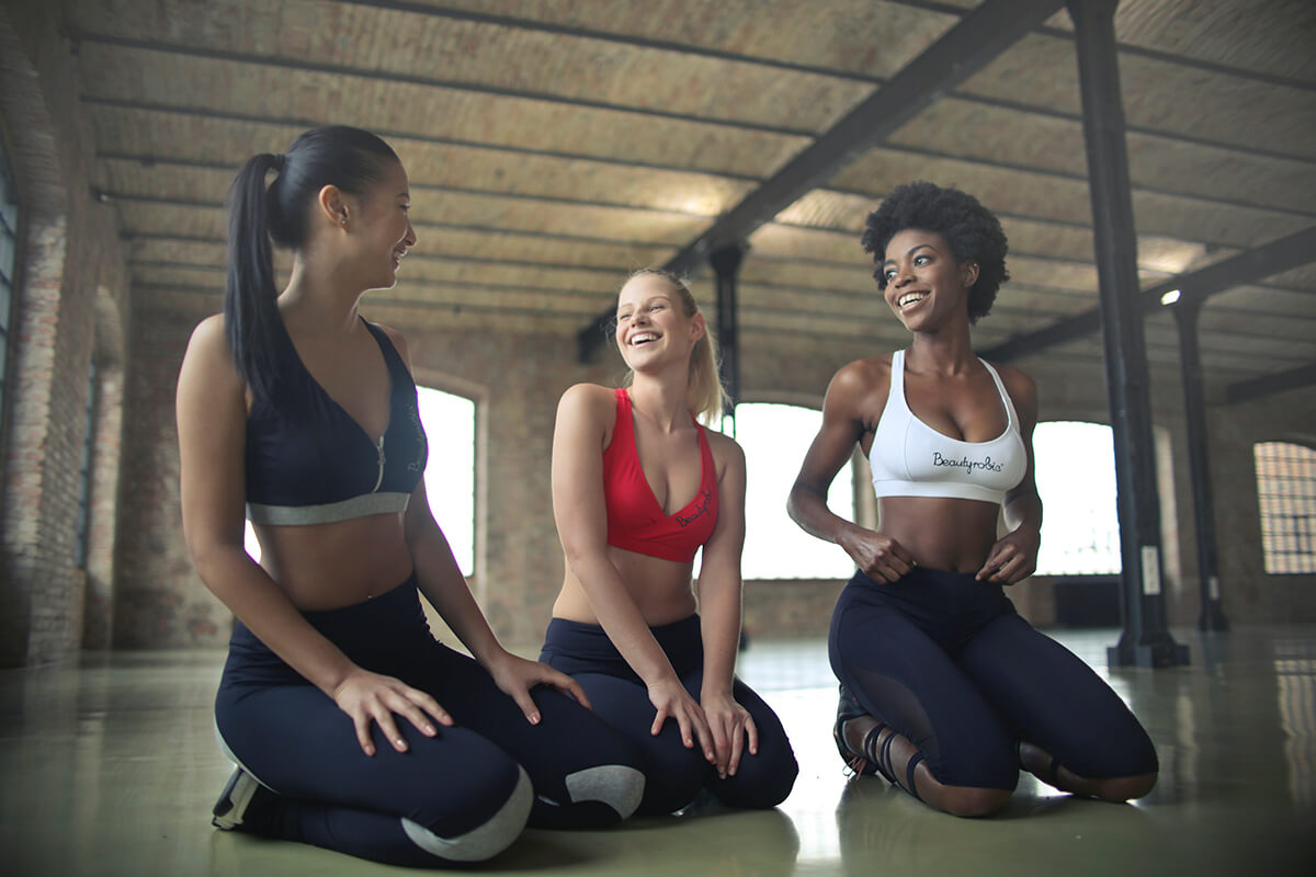 is it healthy to have a low body fat percentage three girls laughing and looking at each other