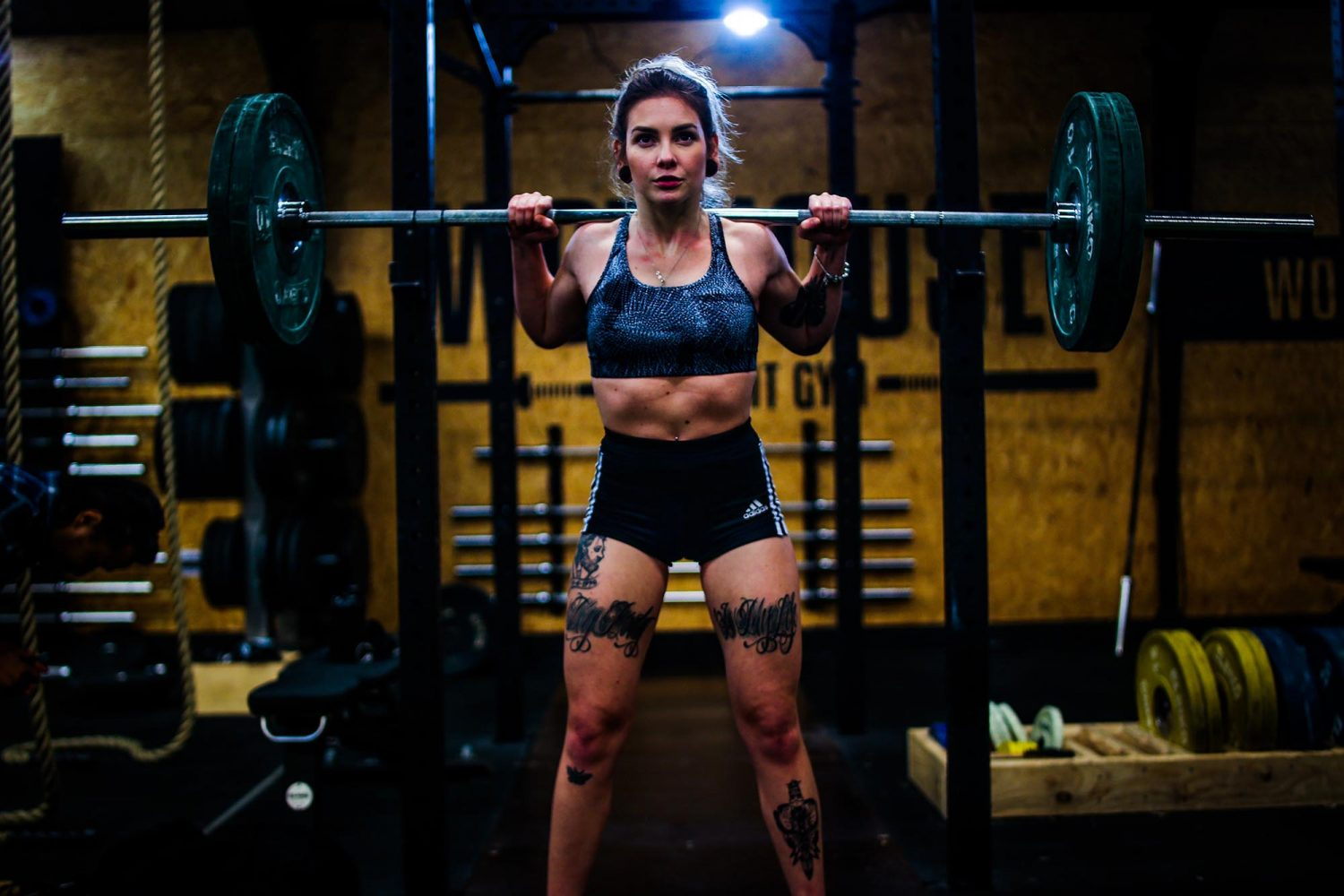 Woman with tattoos preparing to squat in gym